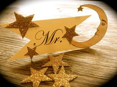 This set of Mr. and Mrs. Wedding Seat Signs feature hand cut crescent moons with stars placed atop a ribbon cut paper banner. The stars are hand glittered with 14 Karat gold glass glitter.  The moon and star illustrations are professionally printed on a premium glossy cover paper and placed atop a beautiful premium matte cover paper. The back of the moon and stars are printed in black and white with a detail of a vintage music sheet. The back of the ribbon cut banner is accented with a small…