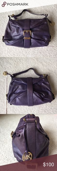 Michael Kors purple handbag Beautiful purple Michael Kors hangbag. This has only been used twice and you can see how nice it is in the pictures. There are no marks or stains on the inside or the outside of the bag. All of the hardware and buckles are gold. There is a zipper closure on the top of the bag. The inside has a zippered pocket and four open pockets as well as a clip for your keys. Michael Kors Bags Shoulder Bags