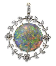 Opal and diamond brooch pendant, circa 1915, centring on a round cabochon opal weighing approximately 9.50 carats within an openwork frame highlighted by old European cut diamond set foliate motifs, mounted in 15ct gold and platinum.