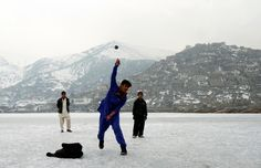 An Afghan boy throws a cricket ball on a frozen lake in Kabul, on February 2, 2012.