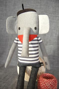 Jean Luc - Soft toy - Jean Luc comes from Provence and sticks his long trunk like in red wine bottles. Although he loves the sumptuous food, he still fits into his skinny jeans. Très bien! - Nikoki Shop