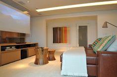 Aconchegante e contemporâneo, o home theater com 24 m² foi mobiliado pela arquiteta Deborah Roig com duas chaises de couro, que também servem para os momentos de leitura. Embaixo da placa de vidro, que divide o ambiente e serve de telão, um rack de madeira comporta os equipamentos