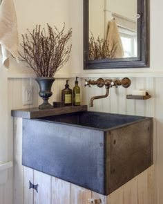 This beautiful powder room sink was salvaged from a chemistry lab and is made of soapstone. The surrounding cabinet is made of old metal, stripped of its paint, leaving an interesting wood-like patina. The shelf to the left of the sink is a piece of left over counter top from the kitchen and is made of honed Irish stone. A great combination of materials and creativity. The builder was Houses and Barns by John Libby of Freeport, Maine. The house is also in Maine.