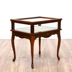 This Queen Anne style end table is featured in a solid wood with a glossy cherry finish. This side table has cabriole legs, curved base trim and a glass lift up top display case. Perfect for displaying knick knacks! #european #tables #endtable #sandiegovintage #vintagefurniture