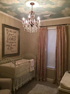neutral nursery with chandelier & clouds on ceiling