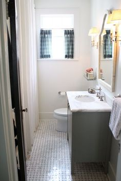 Floor Tile: White Marble Basketweave with Delorean Gray grout   Wall Tile: 3 x 6 Gloss white subway with white grout   Countertop: Honed Calcutta Gold   Sconces: Visual Comfort (polished nickel)