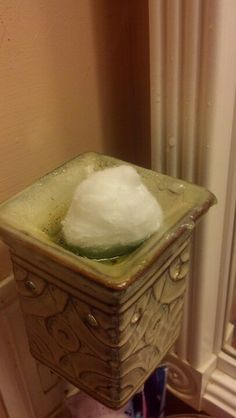 Place a cotton ball in your melted wax and watch it absorb before your eyes, after it's absorbed throw it away. Easy way to switch scents. Genius!!!  So much easier than wiping it with paper towels!