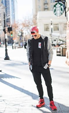 With black t shirt, gray and black jacket, red printed cap and red sneakers