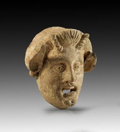 Terracotta mask of Pan. Oval face with wide opened eyes and carved pupils, wide opened mouth with teeth and large, pointed ears and horns above the forehead. Magna Graecia, 3rd - 2nd century B.C. Small damages, tip of the left ear is missing.