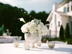 The Sonnet House weddings. Photo by Jett Walker Photography | White guest table centerpieces in mercury glass with votive candles