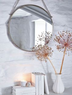 A strikingly stylish vintage style mirror, hung on a simple metal chain.