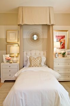 Twin bed with tufted headboard and sunburst mirror and non matching nightstands.