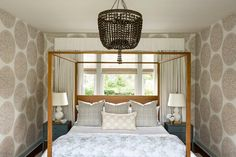 A brown beaded chandelier illuminates a bedroom boasting a borwn wood canopy bed complemented with white and gray bedding topped with a tan medallion pillow layered in front of gray pillows. Grey And White Bedding, Gray Bedding, Wood Canopy Bed, Transitional Bedroom, Design Firms, Portfolio Design, Contemporary Furniture, Home Furnishings, Interior Design