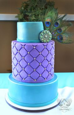 Turquoise and purple wedding cake with peacock feathers (would look better without the feathers!)