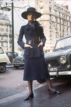 A model displays a long navy blue tailor suit, wide belted long jacket with two patch pockets, scarf and hat in Paris for Christian Dior 1970 Spring/Summer haute-couture collection.