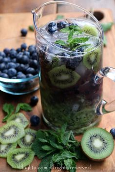 Kiwi Blueberry Mojito 6 kiwis, peeled and cut in half or quartered 4 kiwis, peeled and sliced - to be used as garnishes 6 ounces of blueberries, to be crushed 6 ounce of blueberries, to be kept whole as garnishes ¼ cup fresh lime juice, from 1-2 limes ~ ½ cup sugar, adjust to taste 4 ounce pack of mint, leaves only 1 ½ - 2 cups of sparkling water 1 to 1 ½ cups of rum Ice as needed Blue and/or green sugar to decorate glass rims