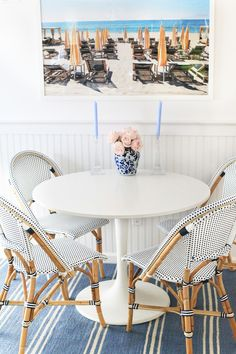 Cosy and pretty breakfast table with cafe chairs and summer inspired artwork