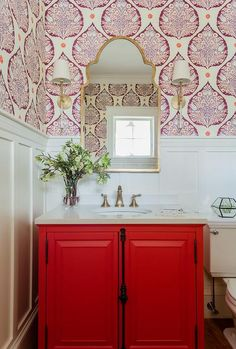 Red and white powder room features half board and batten wall accented with Galbraith & Paul Lotus Wallpaper lit by Camille Long Sconces mounted on either side of a gold arch mirror.