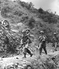 A soldier of the Army of the Republic of Korea wounded in action against the North Korean Communists, is carried to a first aid station by a U.S. infantryman for treatment.