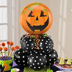 DIY a jolly jack-o'-lantern centerpiece! Stack two layers of four balloons tied together & top them off with a foil pumpkin balloon! A spray of green & orange ribbon will add the finish gourg-geous touch!