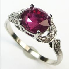 Ruby Crescent: The charm of this vivid red ruby pulls you in with its mesmerizing glow. A pair of diamond set crescent moon shoulders cushion the fiery ruby in a soft embrace drawing the oval shape of the gemstone across the finger. Ca 1930. Maloys.com