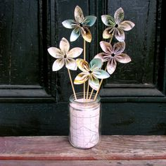 Ingenious! Folding maps to make these beautiful flowers. Hot gluing them to bamboo skewers and arranging them in a vase.  Great, cheap, and very pretty.