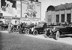 Autokilpailuiden lähtötunnelmia rautatieaseman edessä 1920-luvun alussa. Helsinki, Mainosseinä ja autot