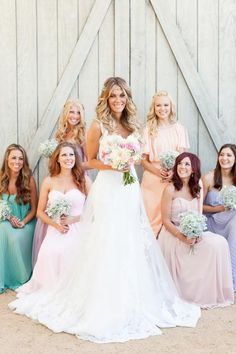 We love how this stunning photo highlights the venue, the bride's beautiful lace gown, her pastel posse, and their adoring looks all in one.Related: Mix