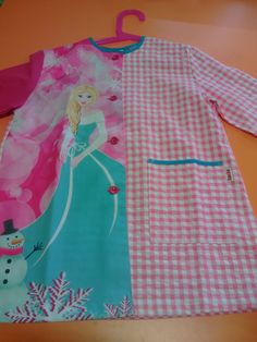 Bata infantil Colegio.  Estampado motivo princesa de hielo.Cierre botones y un bolsillo lateral.Puños elásticos. Color rosa chicle.