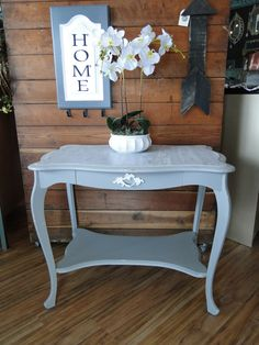 This stylish table was painted in a gray blue with a Faux bois top in a white glaze.