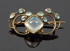 An Arts & Crafts moonstone and enamel brooch, attributed to Jessie M King, 1873-1949, for Liberty & Co., marked 15ct, signed 'L & Co.'