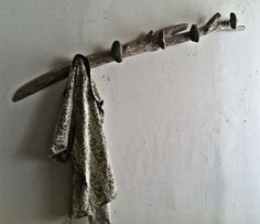 Driftwood coat / towel rack with beach stones offset from wood.  $ 125.00
