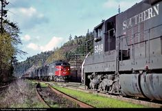 """Three Alco PA's rush SP's first section of Train 11, """"Cascade,"""" past Canby where it met Extra 5349 in the siding, 25 miles out of Portland, Ore., on April 11, 1964. Tomorrow the train will reach Oakland, Calif."""