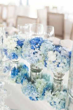 A mix of blue blooms in mercury glass containers reflect against the mirrored table.