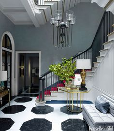 Vivid red carpet on the stairs and a black-and-white marble floor with boldly scaled octagons establish the entry's dynamic mood. Gambrel designed the large Viennese-inspired Suffolk chandelier, part of his lighting collection for Urban Electric. The custom banquette was made by Dune. Eric Piasecki  - HouseBeautiful.com