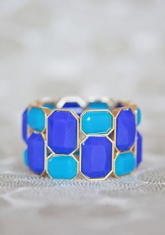 """Ocean Blues Bracelet 16.99 at shopruche.com. Shimmering with the colors of foamy seas, this golden hued bracelet is perfected with faceted blue beads for light-catching charm. Elasticized band.1.75"""" wide, ,"""
