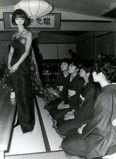 """""""Japanese Fashions are in the time of the Tokyo Olympics the highlight of the International Fashion Week in Düsseldorf. This evening dress 'Obi', made of the same material as the famous kimonos, was designed by the fashion-advisor of the Empress of Japan."""" Press release, dated 24.10.64  Hiroko Matsumoto was a famous fashion model and style icon of the 1960s. She was the muse for much of the early work of Pierre Cardin and in 1970 she appeared in François Truffaut's film """"Domicile Conjugal""""."""