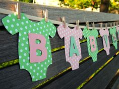 Tendero de baby shower decorado con ropa de bebe de cartulina decorativa.