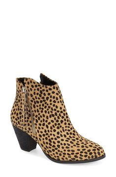 A tasseled zip pull adds flirty movement with every step in this stacked-heel bootie styled with a wing-cut topline in a fun cheetah print.