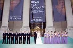 large bridal party wearing purple in front of museum