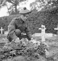 Private E. Eastle of The Black Watch (Royal Highland Regiment) of Canada at the grave of his brother, who was a member of The Royal Highland Light Infantry of Canada. Ossendrecht, Netherlands, 26 October 1944.