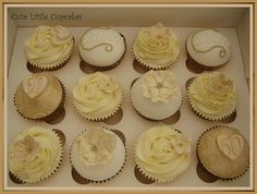 A box of 60th birthday cupcakes made up of vanilla and raspberry & white chocolate, decorated with a subtle gold theme.