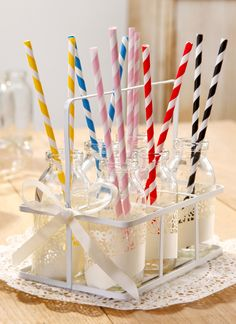 A selection of colourful straws from Talking Tables displayed in cute mini milk bottles decorated with Ivory Cake Wraps. A creative and useful party table display! #talkingtables #inspirational