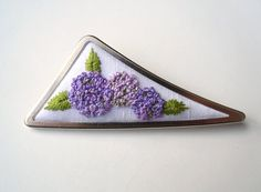 An embroidered brooch featuring lovely hydrangeas in a variety of mauves / purples with green leaves on a white fabric. All lovingly hand embroidered by