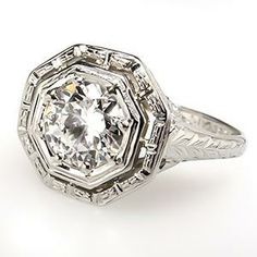 $4,999.00  This gorgeous art deco solitaire engagement ring features a magnificent .86 carat transitional cut genuine diamond grading G in color and VS1 in clarity. This ring has intricate detailed openwork and filigree and is crafted of solid 18k white gold.