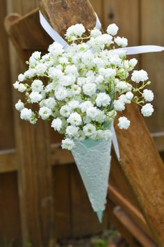 hang the cone on the back of bridemaids chair for them to place your flowers in
