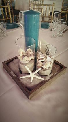Simple but cute beach themed centerpiece| cylinder vases| beach shell and sand…