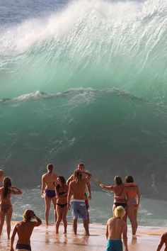 Famous Waimea Beach, North Shore Oahu. Waves are 20ish feet. Looks like they are about to get pounded. But it's an illusion. The sand slopes down from where they stand, and the water is several feet away.