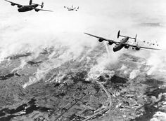 On this day in history: B-24 Liberators of the 460th Bomb Group flying from the Foggia Airfield complex in Italy bombing the railroad yards in Klagenfurt Austria 27 December 1944. The smoke is from smudge pots lit to obscure the target.