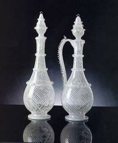 Small bottles in reticello decorated with wavy threads of vitreous paste and crests along the handle. As usual, each mesh of the netted filigree encloses a tiny air bubble locked in the crystal wall.